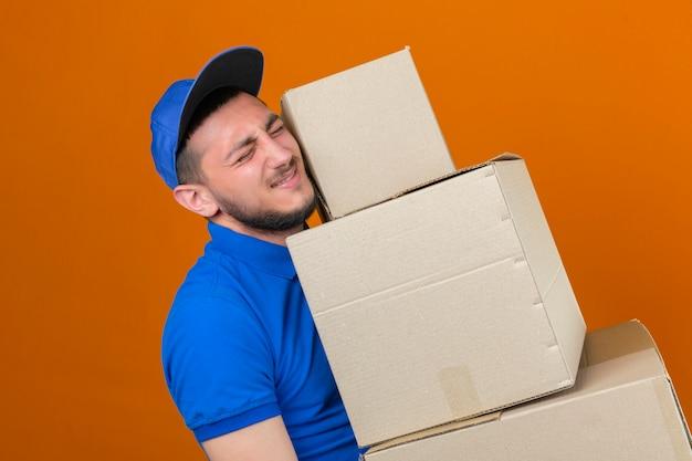 Les jeunes plus tendu livreur portant un polo bleu et une casquette debout avec pile de boîtes à la fatigue sur fond orange isolé