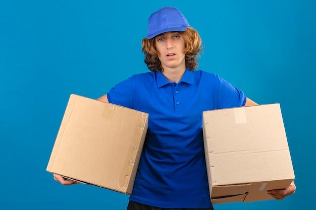 Les jeunes plus tendu livreur portant un polo bleu et une casquette tenant des boîtes en carton à la fatigue debout sur fond bleu isolé