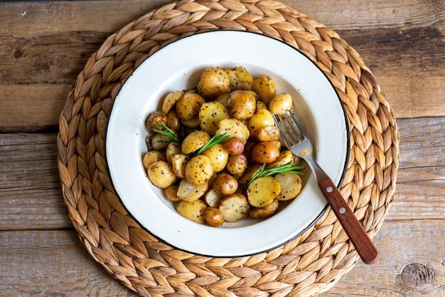 Jeunes pommes de terre au four au romarin. cuire au four et faire frire les jeunes pommes de terre dans une poêle. petites pommes de terre au beurre et aux herbes. un concept de cuisine rustique. patates frites.