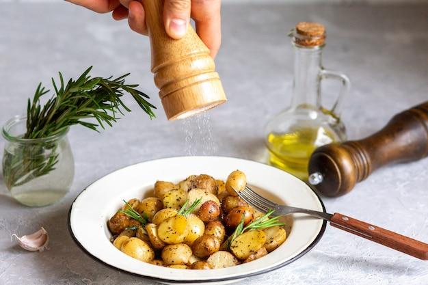 Jeunes pommes de terre au four au romarin. le sel saupoudre sur le plat. cuire au four et faire frire les jeunes pommes de terre dans une poêle. petites pommes de terre au beurre et aux herbes. un concept de cuisine rustique. patates frites.
