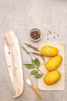 Jeunes pommes de terre crues et filets de merlu surgelés aux herbes et épices