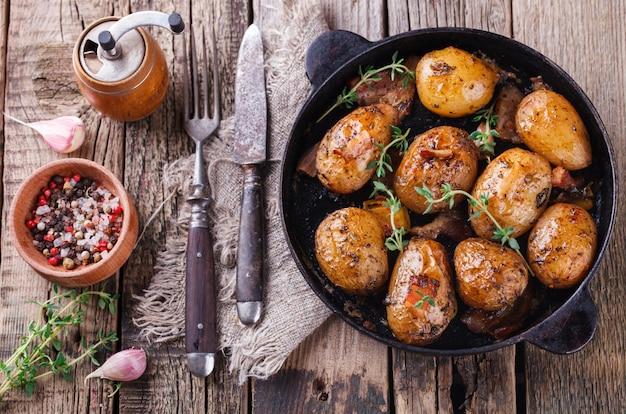 Jeunes pommes de terre frites dans une poêle. à l'ail, pancetta