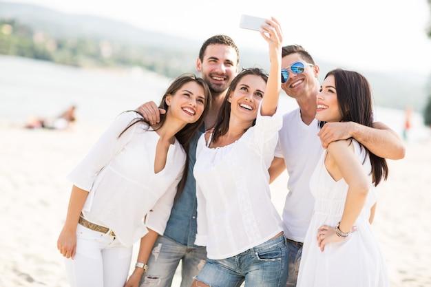 Jeunes prenant des photos sur la plage