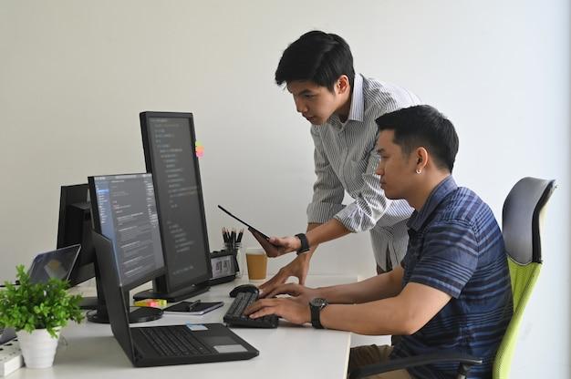 Jeunes programmeurs travaillant sur ordinateur et tablette en milieu de travail de bureau moderne.