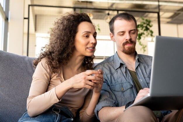 Jeunes propriétaires de restaurant luxueux ou de café confortable assis sur un canapé et discutant d'idées en ligne