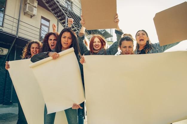 Des jeunes protestant contre les droits des femmes et l'égalité dans la rue. les femmes de race blanche ont une réunion sur le problème sur le lieu de travail, la pression masculine, la violence domestique, le harcèlement. espace de copie. tenir des affiches.