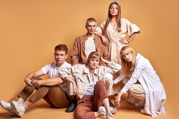 Les jeunes de race blanche sont assis ensemble sur le sol isolé sur brun, portant les mêmes tenues élégantes