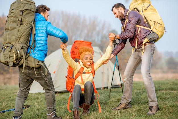 Jeunes randonneurs masculins aidant une femme à se lever avec des sacs à dos colorés sur la pelouse verte près du camping