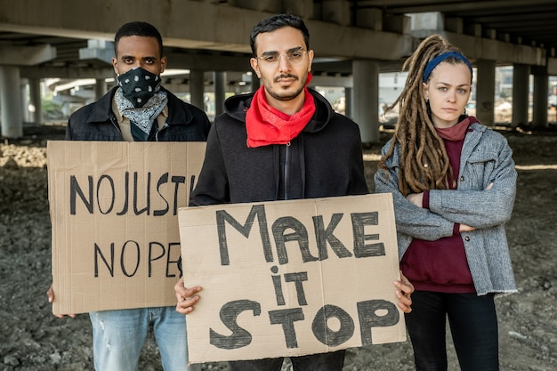Jeunes rebelles multiethniques confiants debout avec des pancartes et protégeant contre l'injustice du gouvernement
