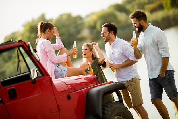 Jeunes s'amusant en voiture décapotable au bord d'une rivière