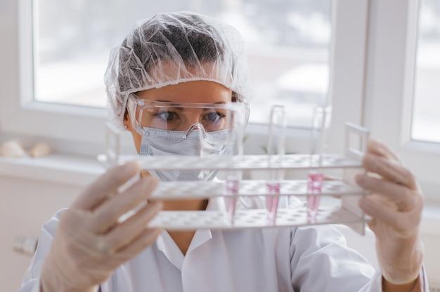 Jeunes scientifiques avec des tubes à essai faisant des recherches en laboratoire clinique