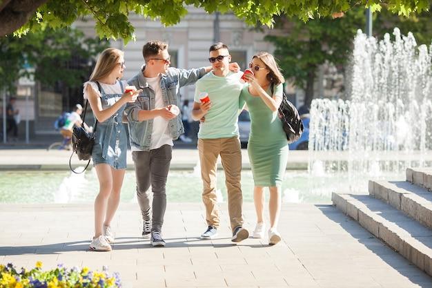 Les jeunes se promènent dans la ville. des amis élégants s'amusent ensemble. groupe de personnes buvant du café et parlant.