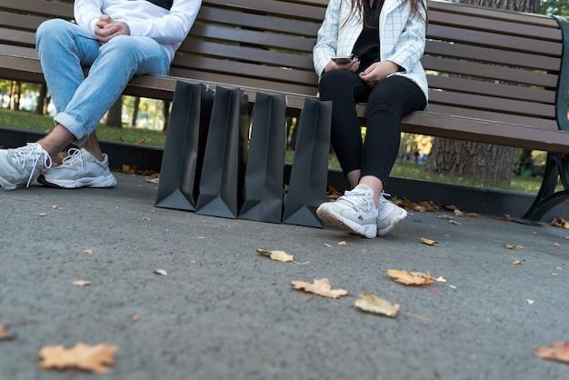 Les jeunes se reposant sur un banc dans un parc avec des sacs en papier. couple après le shopping. tout juste marié