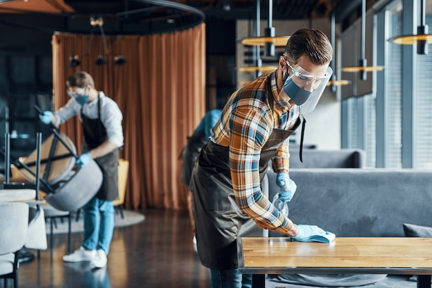 Jeunes serveurs masculins occupés dans des vêtements de travail protecteurs pulvérisant du désinfectant sur les tables du restaurant