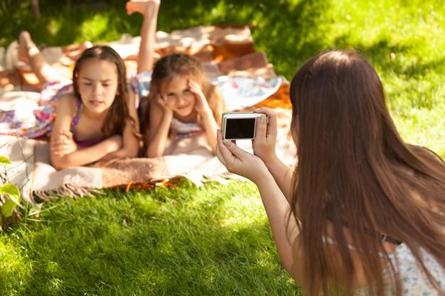 Jeunes soeurs mignonnes se trouvant sur l'herbe et posant pour la photo