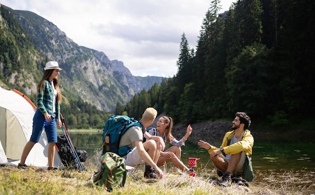 Jeunes souriants profitant de la nature à côté des tentes et parlant en plein air