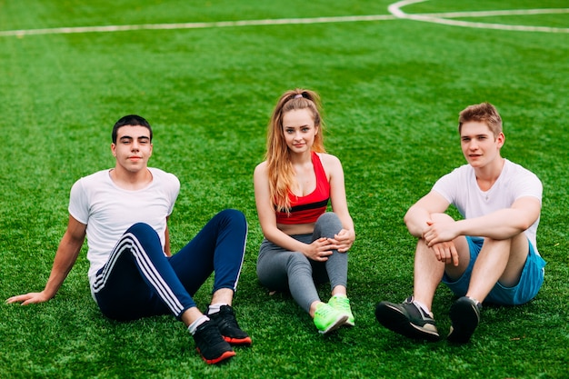 Jeunes sportifs assis sur l'herbe
