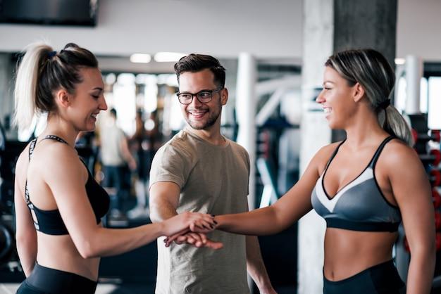 Jeunes sportifs en forme rassemblant les mains dans la salle de gym.