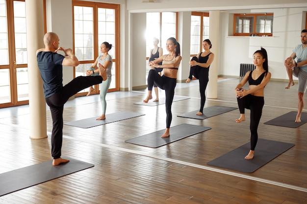 Jeunes sportifs pratiquant le yoga avec instructeur, s'entraînant. cours de fitness, sport et concept de mode de vie sain.