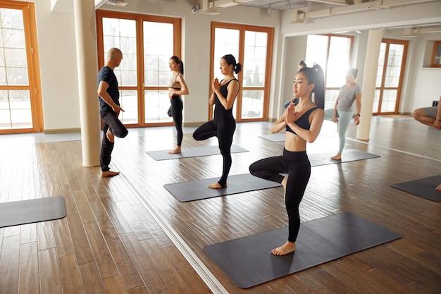 Jeunes sportifs pratiquant le yoga avec instructeur, s'entraînant. notion de bien-être.