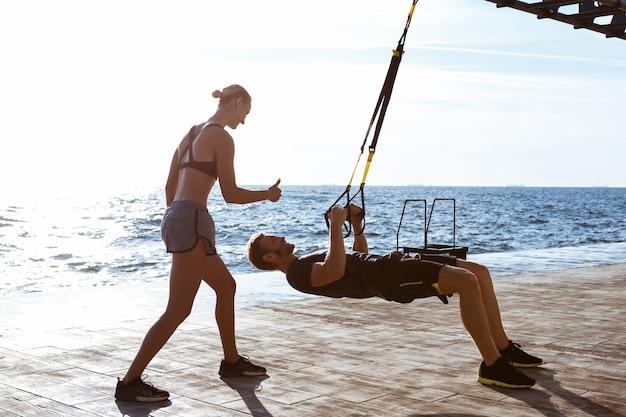 Jeunes sportifs s'entraînant avec trx près de la mer le matin.