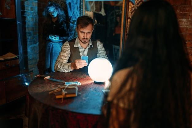 Jeunes à la table avec boule de cristal