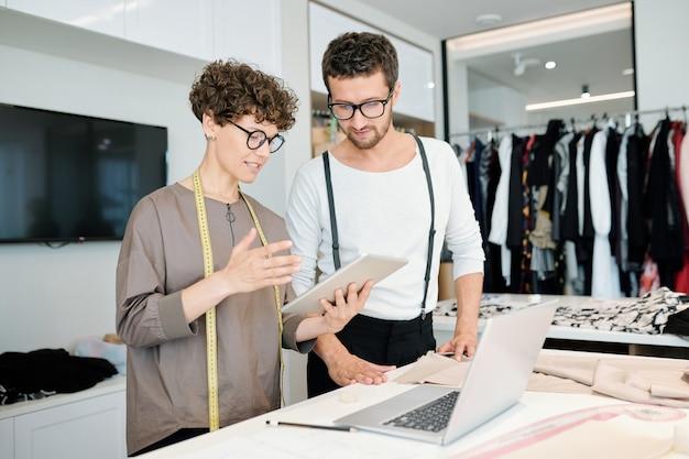 L'un des jeunes tailleurs avec tablette faisant la présentation d'idées pour une nouvelle collection de mode tout en se tenant debout près du bureau