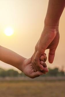 Jeunes tenant par la main au coucher du soleil.