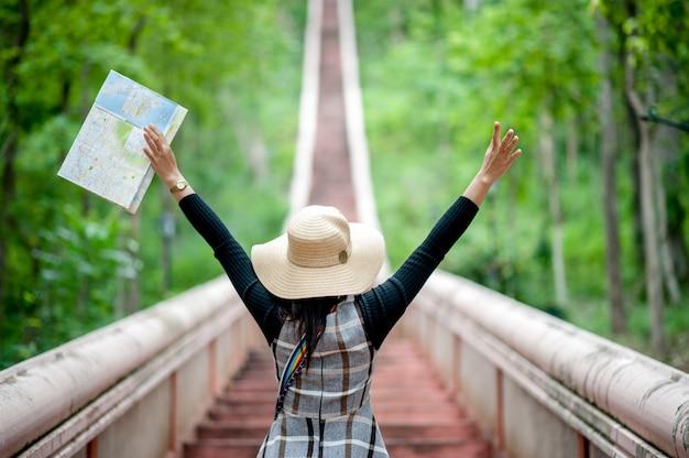 Les jeunes touristes et une carte avec un sourire sont heureux de voyager à divers endroits.