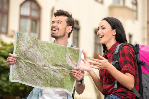 Les jeunes touristes avec carte touristique se promènent dans la ville.