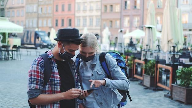 Jeunes touristes dans des masques de protection et avec des sacs à l'aide de smartphone. ils recherchent des attractions touristiques intéressantes.