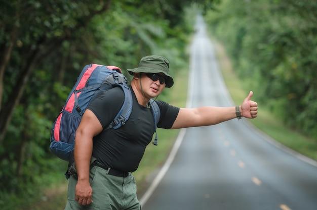 Jeunes touristes masculins portant un sac à dos pour voyager en auto-stop. voyagez en auto-stop. des touristes attendent pour faire de l'auto-stop ou demander de l'aide au bord de la route dans la forêt du parc national de khao yai.