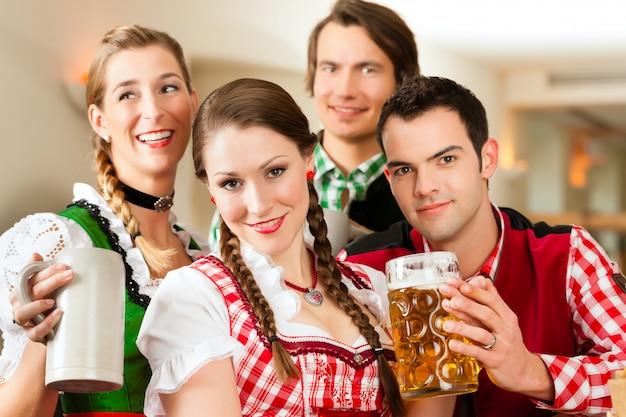 Jeunes en tracht bavarois traditionnel au restaurant ou au pub