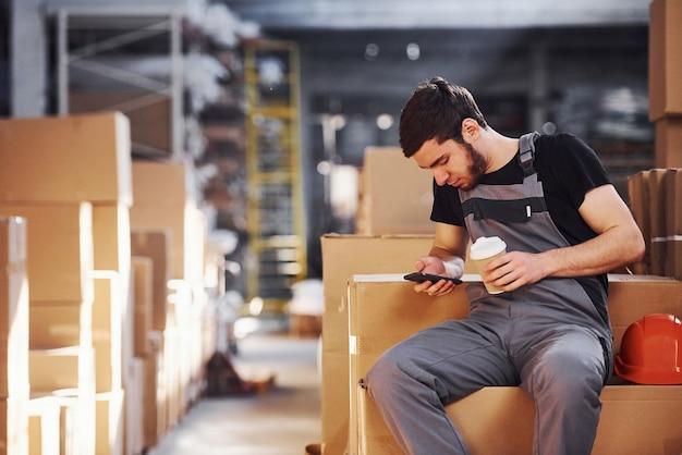 Les jeunes travailleurs du stockage font une pause, assis sur les boîtes avec un téléphone et une tasse de boisson dans les mains.