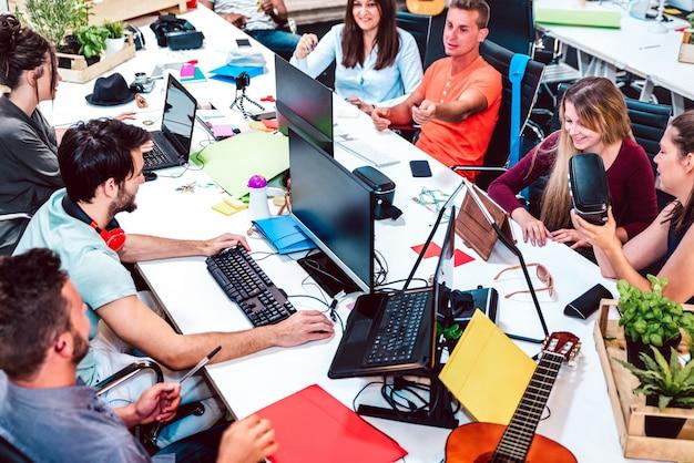 Jeunes travailleurs employés sur ordinateur dans un studio alternatif urbain