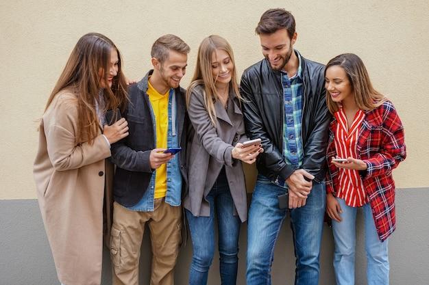 Jeunes utilisant des smartphones - groupe de collaborateurs des médias sociaux s'amusant avec une photo vidéo en ligne -