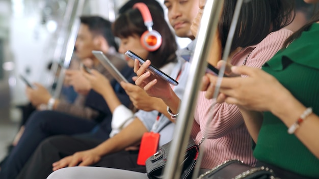 Jeunes utilisant un téléphone mobile dans le métro