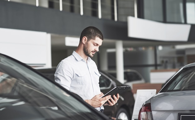 Jeunes vendeurs avec un dossier pour vendre une nouvelle voiture.