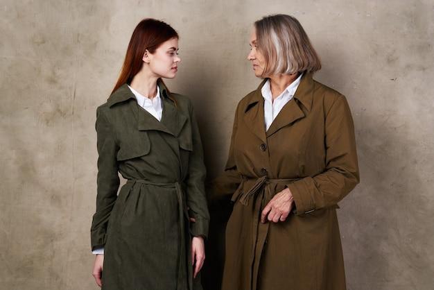 Jeunes et vieilles femmes se tiennent côte à côte studio de mode automne fond isolé