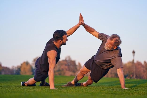 Les jeunes et vieux sportifs poussent ensemble sur l'herbe