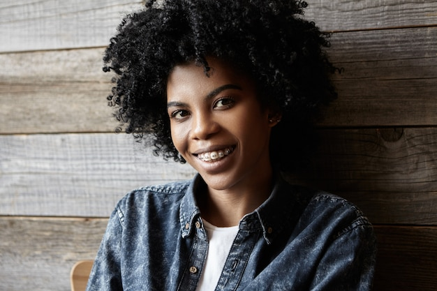 Jeunesse et bonheur. beauté et mode. bouchent le portrait de l'heureuse jeune femme africaine attrayante avec des accolades profitant de son temps libre à l'intérieur au café moderne, habillé en chemise de jeans à la mode