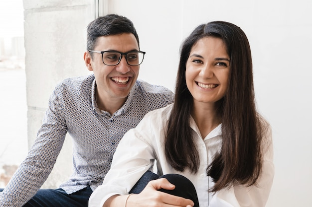 La jeunesse moderne est assise à la fenêtre. le gars et la fille rient joyeusement. couple d'amoureux s'amusent