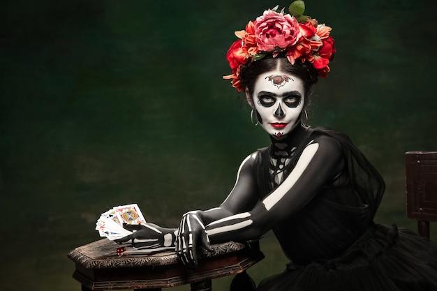 Jeux d'argent. jeune fille comme la mort de santa muerte saint ou le crâne de sucre avec un maquillage brillant. portrait isolé sur fond de studio vert foncé avec fond. célébrer halloween ou le jour des morts.