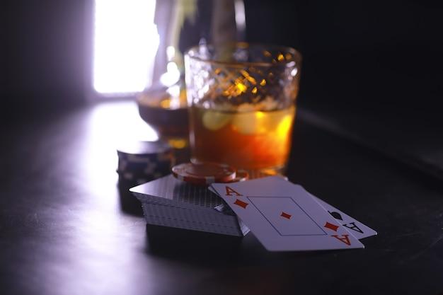 Jeux de cartes pour de l'argent. texas hold'em poker. cartes en main, jetons de jeu, jeu de cartes d'alcool dans un verre.