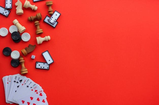 Jeux de société sur fond rouge: cartes à jouer, dominos, pions et échecs. la vue du haut, placez sous le texte