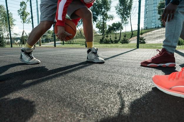 Jeux sportifs. gros plan d'une balle orange dans les mains des joueurs de basket-ball