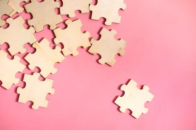 Jigsaw puzzle sur fond rose, vue de dessus.