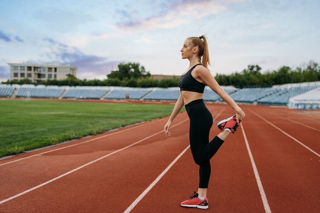 Jogger féminin en vêtements de sport, entraînement sur stade. femme faisant des exercices d'étirement avant de courir sur une arène extérieure