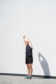 Jogger homme de race blanche porté en tenue de sport noir qui s'étend avant de courir près du mur blanc, profitant de la lumière du soleil