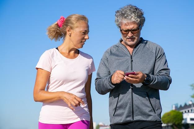 Jogger masculin ciblé utilisant l'application de fitness sur téléphone portable après le jogging. couple d'âge mûr portant des vêtements de sport, debout à l'extérieur. communication et gadget pour le concept de sport